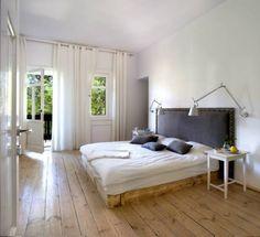 """Główna sypialnia z bieloną podłogą i łóżkiem, którego rama zbita z surowych desek, i na zasadzie kontrastu opatrzona """"pałacowym"""" zagłówkiem,..."""