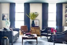 A Donald Sultan painting surmounts a chest of drawers in the living area, while a framed Polly Borland tapestry hangs on the wall at far left; the dark leather armchairs are vintage Arne Norell designs from Emmerson Troop, the bronze side tables are by Stephanie Odegard Collection, and the carpet is by Doris Leslie Blau.