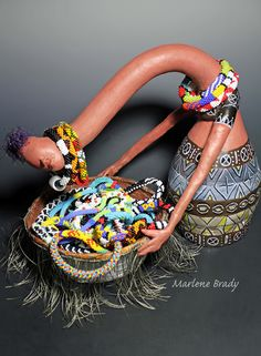 Marlene Brady. The elongated necks of the tribal women of Kenya inspired my gourd sculpture display for my bead crochet--bracelets on her neck and necklaces in the basket.