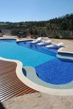 Em formas arredondadas, esta piscina projetada e construída pela Planeta Água com estrutura de concreto armado tem prainha e banco. O revestimento interno é de pastilhas de vidro