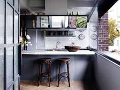 Robert and Susan's converted '20s harbour view apartment:A collection of glossy black lacquerware from Burma sits above the dish-rack shelves in the kitchen.
