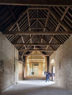 This glazed house-shaped gallery sits within an old barn in a English village without appearing to touch the floor, the thick stone walls or the timber-truss roof.