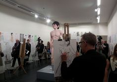 shrigley's 'life model' — a participatory art experience that invites members of the public to draw a giant sculptural nude boy located on a plinth in the center of the room. the space is set up like a university 'life-drawing' class. his over-sized ears and nose take up much of his face, his animatronic beady eyes blink, and occasionally, he urinates into a metal bucket near his feet.