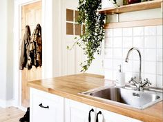 20+Things+You+Need+to+Toss+Before+The+New+Year:+Say+goodbye.+via+@domainehome kitchen -wood counters, white cabinets, white tile backsplash, faucet.