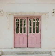 A lovely set of double doors in a soft pink and iron scroll work in white.  Very feminine.