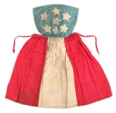 c. 1861-1865, Confederate apron, made & worn by a young girl, Martha L. Booton.  Made out of scraps from a flag created for soldiers from Page County.  Cotton cloth apron features a blue bib with seven five-pointed stars; skirt has alternating bars of red & white cotton.  Composition mimics the flag adopted by the Confederacy in 1861.