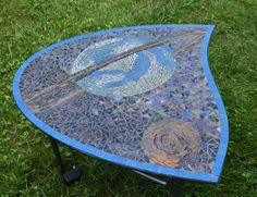 Saturn Glass Mosaic Tabletop  Whimsical take on Saturn with rings and moon, this is a vitreous glass mosaic on a glass base. The tabletop is a curvy teardrop shape, or perhaps a cut-off oval better describes it. The base is metal, with three legs, and has been outfitted with a strip of LED