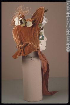 Bonnet, circa 1860, velvet, high open brim decorated with silk bows, flowers and leaves, repeated on top with plumes, the exposed face would have meant a parasol used on sunny days, McCord Museum