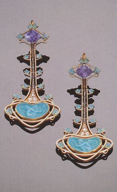 René Lalique - A fine pair of Art Nouveau gold, enamel, diamond, sapphire and turquoise 'Cupid' earrings, 1903-05. Each set with a lozenge-cut sapphire within leafage enamelled in pale turquoise above an undulating support set with old mind diamonds above a kidney-shaped turquoise carved with a cupid within a white-enamelled whiplash surround. Signed. 5cm long. Source: Sotheby's Important Jewellery, Geneva, 20 January 1996.