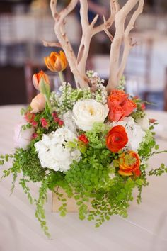 Such a great nature inspired centerpiece....bright foliage and flowers at the base of a manzanita branch.