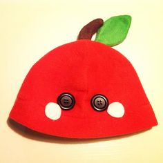 An apple beanie/plushy hat! It's made out of soft, kind of stretchy polar fleece! The leaves, pink blush marks and the stem are made out of felt, and is either securely hot glued on or sewn in. The eyes are black buttons, and are also securely affixed with hot glue.    The hat would fit on a head...