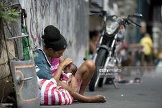 Homeless woman Inday Ibayo (L), 30, holds her one-month-old baby along a street in Manila on August 28, 2014. The Philippine economy rebounded to post 6.4-percent growth in the second quarter and regain its status as one of the strongest in Asia, authorities said on August 28. Officials said in April that amongst their new targets is the lowering of the country's poverty incidence from 25.2 percent of the population in 2012 to 18.0 to 20.0 percent by 2016.