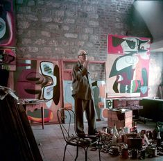 Le Corbusier stands in his Paris apartment, surrounded by paintings, in 1953. This and other rare color images shot by Willy Rizzo are on view in an exhibition this month. | Ultra Rare Photos Of Le Corbusier In Color | Co.Design: business + innovation + design