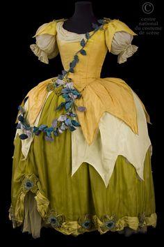 * Une jonquille costume pour les Indes Galantes de Jean-Philippe Rameau Robe à paniers en soie de différents tons de jaune et en voile bronze, garnie de guirlandes de feuilles artificielles vertes 1952