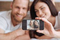People Stock Images , People Pictures , person photo , - Young couple taking self portrait picture with smartphone