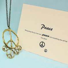 A unique golden tone peace necklace that comes with a unique quote card. The pendant has 5 peace symbols of varying size all of which have