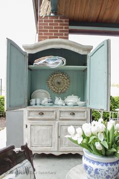White washed rustic armoire with blue interior and planked back, filled with ironstone