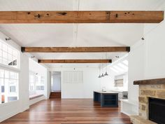 Stritt Design & Construction | Avalon Village Residence. Hamptons style. Open plan living room. Recycled hardwood beams with V-Joint panelled ceiling and sandstone fireplace. Reclaimed ironbark timber flooring.