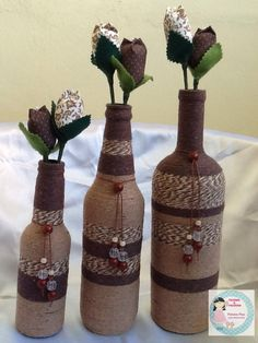 trio of upcycled bottle vases  ...  wrapped with twine and baker's twine in brown tones  ... fabric/paper flowers ...