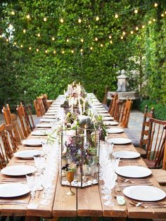 Courtyard dinner party setup with strung lights and long wood table
