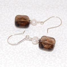 Beautiful genuine Smoky Quartz faceted square pillows are accented with creamy white fresh water pearls, and sterling silver. Ear wires are hand-formed with sterling silver. Measures 1 1/2 inches in length from top of ear wire to bottom of bead. These will be made to order and promptly shipped.