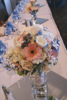 Example of using wedding party bouquets for table decorations instead of purchasing additional arrangements. Bride's bouquet contains Vendela white Roses, pink mini Gerbera Daisys, light blue Delphinium, white Lisianthus, Stephanotis and varigated Pittosporum. I designed these.