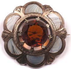 Here's a lovely quality Victorian era Scottish Cairngorm brooch. The piece features a prong set Citrine stone in the center with six Montrose Agate demi-lune stones set around it in an engraved silver