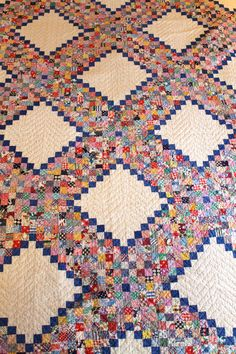 This quilt was made out of flour sacks in the 1930s or 1940s. The quilt measures 76 x 79 and each square is 1.