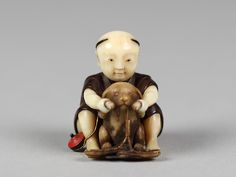 Netsuke of Boy Playing with a Dog Date: 19th century Culture: Japan Medium: Wood and ivory Dimensions: H. 1 1/4 in. (3.2 cm)