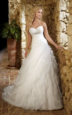 Stella York - 5664 This sophisticated designer A-line bridal gown is hand crafted with soft, flowing Organza. The gown's skirt features an asymmetrical pattern that flatters every figure. Dress is shown with a sheer cap sleeve jacket with crystal embellishments, available separately.