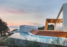 Five cliff-top buildings feature walls that fold in on themselves to frame views and offer privacy in this South Korean holiday resort.