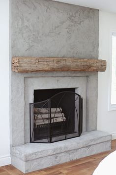 House Update: Real Antique Wood Ceiling Beam - Lindsay Marcella : concrete fireplace with reclaimed wood mantel Stucco Fireplace, Brick Fireplace Makeover, Concrete Fireplace, Bedroom Fireplace, Farmhouse Fireplace, Home Fireplace, Fireplace Remodel, Fireplace Design, Fireplaces