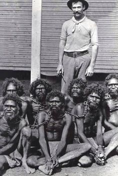 Slave owner and his slaves. Many slaves would be treated like animals, that would explain why they are chained up and look miserable.