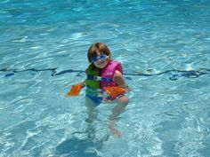 kids swimming flipers on her hands rather then feet