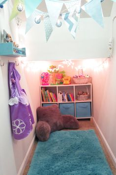 Playroom in a closet under the stairs. Twinkle lights, bue/turquoise. Cubbies. Dress up. Paper banner. Target decor. 10x3 foot space with low ceilings. Check out this blog for more home organization tips for small spaces.