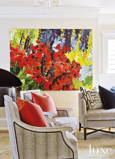 A view of the living room highlights a pair of bergères and gives peek at one of the room's Kravet sofas, dressed in mohair. Custom pillows from GR Home and a large-scale painting by artist Bobbie Burgers,  acquired through Foster/White Gallery, add bold color and pattern.