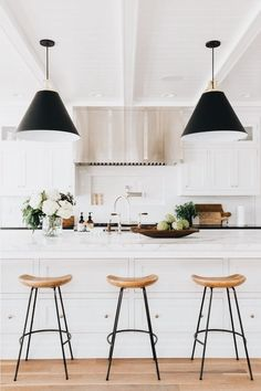 I love the pretty white cabinets, warm wood, and black pendant lights in this beautiful neutral kitchen!