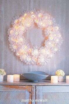 "This delicate-looking wreath is easy to make and surprisingly sturdy: First, the rounded wire frame is strung with twinkling lights that are nestled in frothy, doily-like paper bouquet holders known as ""Biedermeiermanschetten,"" which is a traditional German craft. #marthastewart #christmas #diychristmas #diy #diycrafts #crafts"