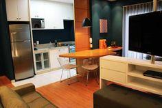 A ideia inicial do morador era fechar a cozinha e isolá-la da sala. Mas a arquiteta Ana Paula Barros achou não valia a pena desmontar tudo e manteve o móvel da mesa de jantar e o painel divisório. O tom azul escuro destaca os móveis e os objetos de design conferem cor ao ambiente.