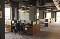 Open space with low walls dividing staff's individual work areas but still keeping them connected visually