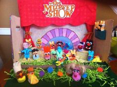 2012 Title: The Mupeep Movie  Description: This diorama, created by muppet lovers Jennifer Weitkamp and Erin Goodling, depicts a scene from The Muppet Movie, where the muppets hold a telethon in order to raise funds to save the Muppet Theater. Kermit sings The Rainbow Connection and his friends join him on stage to support him. Included in the diorama are Kermit, Miss Piggy, Fozzy, The Swedish Chef, Gary, Walter, and many more of their muppet friends.
