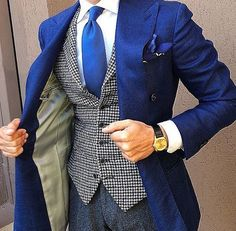 Team a blue double breasted blazer with charcoal dress pants for a sharp, fashionable look. Shop this look on Lookastic: https://lookastic.com/men/looks/double-breasted-blazer-waistcoat-dress-shirt/19978 — White Dress Shirt — Blue Print Pocket Square — Blue Tie — White and Black Houndstooth Waistcoat — Black Leather Watch — Blue Double Breasted Blazer — Charcoal Dress Pants