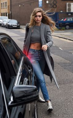 Acheter la tenue sur Lookastic: https://lookastic.fr/mode-femme/tenues/manteau-gris-top-court-gris-jean-skinny-bleu/17711   — Top court gris  — Manteau gris  — Jean skinny bleu  — Bottines en cuir argentées