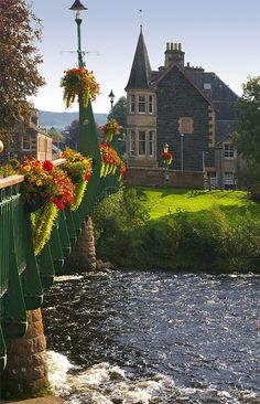 River Earn flows underneath a flower decorated bridge in Comrie, Scotland