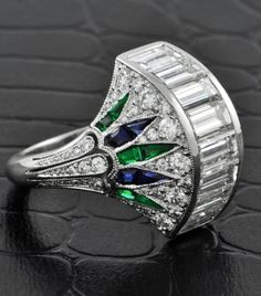 A platinum cocktail ring in an Art Deco-inspired design. The ring features a row of baguette-cut diamonds channel-set at the center of a half-domed mounting. The sides of the dome are pave-set with graduated round-cut diamonds intersected with a fan of tapering foliate plaques set with calibre-cut sapphires and emeralds. The ring shank is similarly decorated with small round-cut diamonds in vintage palmette motifs.