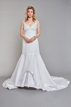 Style #: 16201-6 Giverny Fitted, low-cut, empire waisted gown with delicate straps and a soft gathered bodice overlay. The skirt is layered with silk satin-faced organza and edged with satin piping. The bottom layer of duchess satin is edged with organza piping.