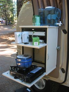 Sportsmobile: Stove - like the idea of an outside kitchen station hung on the inside of an open door...