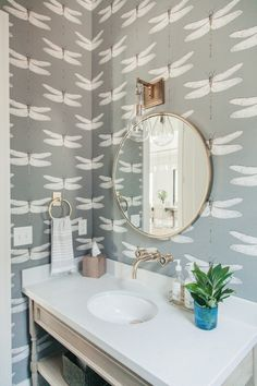 love the fun wallpaper and classic elements in this powder bathroom. brushed brass accents