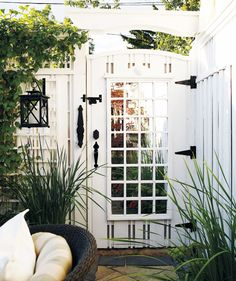 Lattice effect  Built from scrap lumber and fence board, the door is finished with ironwork hardware, and mirror-backed lattice, which is used throughout the space. Mirror visually expands the garden, amplifies light and blurs the line between indoor and outdoor decorating.