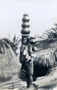 Igorote woman carring water pots and a baby. Igorot are the people of the Cordillera region, on the Philippino Island of Luzon. The smaller group of the Igorot live in the east and north of the Island and formerly practiced headhunting.